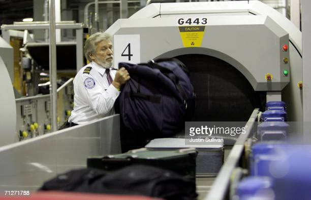 Transportation Security Administration worker monitors bags as they enter an explosive detection system at the Oakland International Airport June 22...