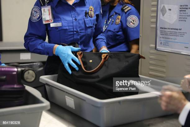 Transportation Security Administration worker screens luggage at LaGuardia Airport on September 26 2017 in New York City Passengers traveling on...