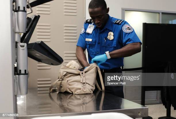 Transportation Security Administration worker screens passengers at LaGuardia Airport on the day before Thanksgiving the nation's busiest travel day...
