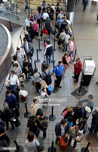 Transportation Security Administration worker stands in the middle of a group of stranded passengers waiting to get screened as normal operations...