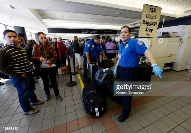 Transportation Security Administration workers screen luggage in Terminal 2 of Los Angeles International Airport as travelers start arriving for...