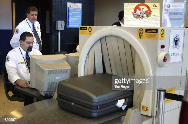 Transportation Security Agency employees Philip Calderon and George Prescott monitor a piece of checked baggage as it passes through an InVision CTX...