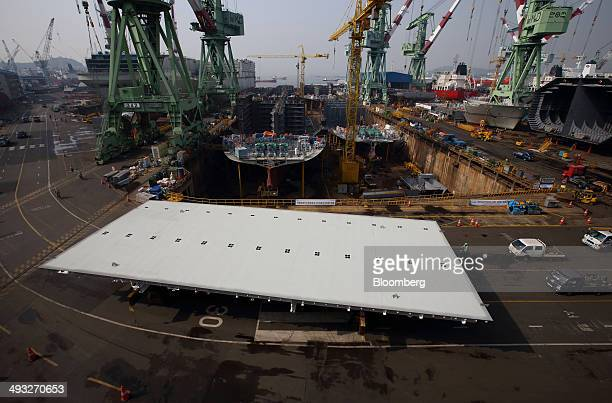 A transporter moves a part of a ship past vessels under construction in the dry dock at the Hyundai Mipo Dockyard Co shipyard an affiliate of Hyundai...