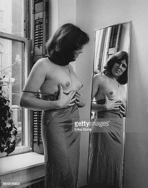 A transsexual examines her new breasts in the mirror after receiving hormone treatment circa 1975