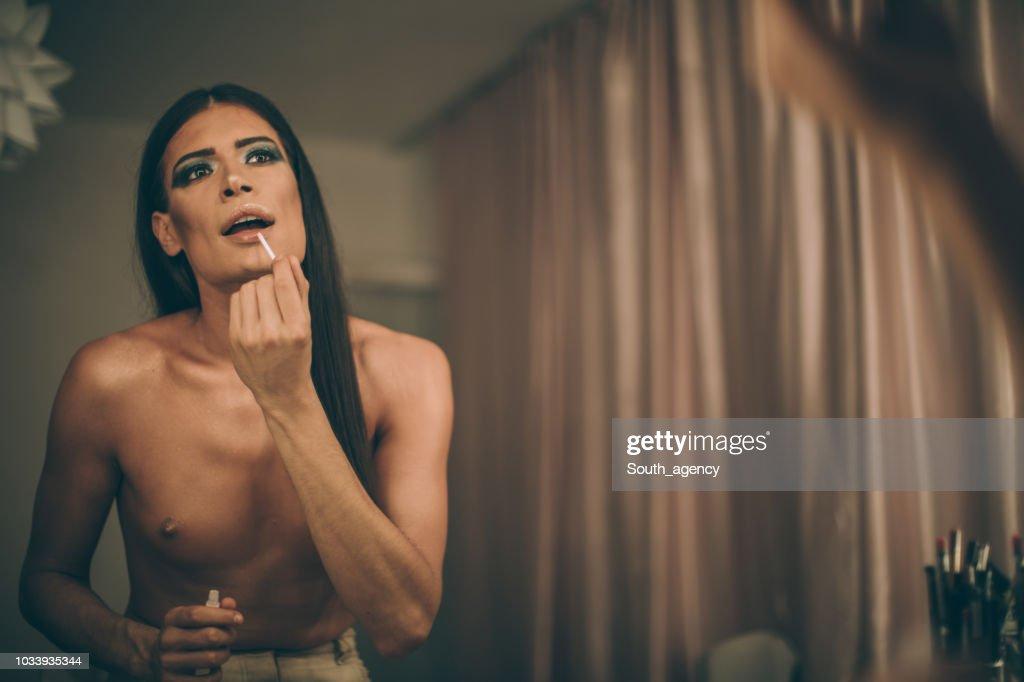 Transsexual man puttinglipstick : Stock Photo