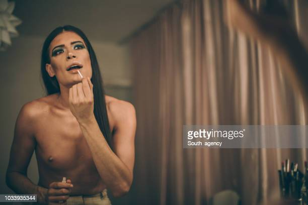transsexual man puttinglipstick - transvestite stock photos and pictures