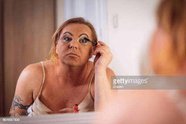transsexual person putting mascara on in front of the mirror at home - transvestite stock photos and pictures