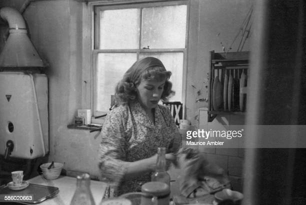 Transsexual Roberta Cowell , formerly Robert Cowell, at work in a kitchen, March 1954. Roberta was once a Spitfire pilot, prisoner of war, racing...
