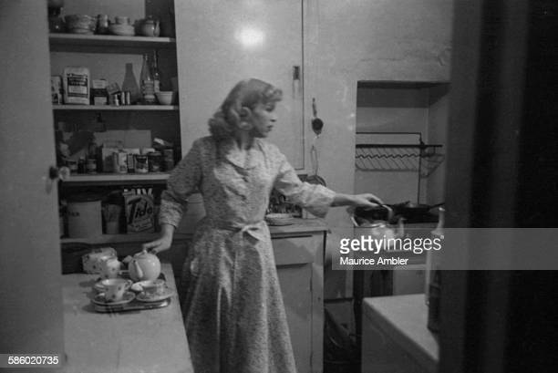 Transsexual Roberta Cowell , formerly Robert Cowell, making tea in a kitchen, March 1954. Roberta was once a Spitfire pilot, prisoner of war, racing...