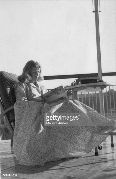 Transsexual Roberta Cowell , formerly Robert Cowell, reading a magazine, March 1954. Roberta was once a Spitfire pilot, prisoner of war, racing...