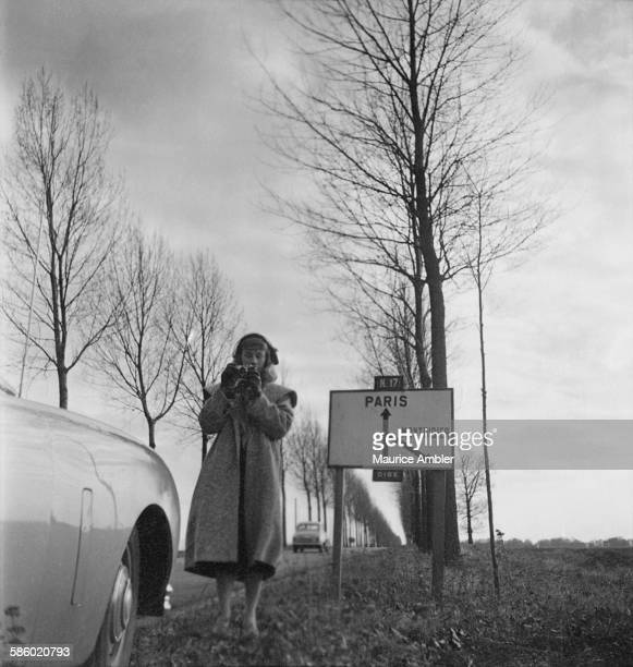 Transsexual Roberta Cowell , formerly Robert Cowell, taking a photograph at the side of Route Nationale 17 to Paris, March 1954. Roberta was once a...