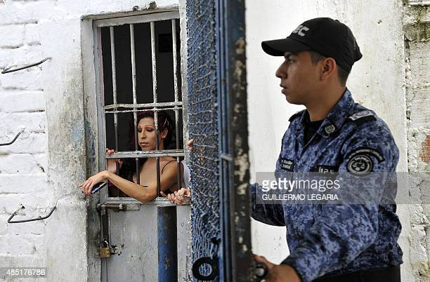 A transvestite inmate gestures from a cell next to a guard at La Modelo prison in Bucaramanga Colombia on August 21 2015 In a prison in the mountains...