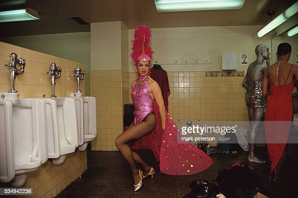 A transvestite named Federika and two other transvestites dress up in the men's bathroom near the urinals during the Love Ball a fundraiser for AIDS...
