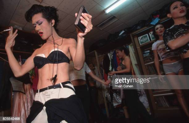 A transvestite performer wearing a stuffed black bra rehearses backstage before a cabaret show at a nightclub in Soi 4 off Silom Road in downtown...