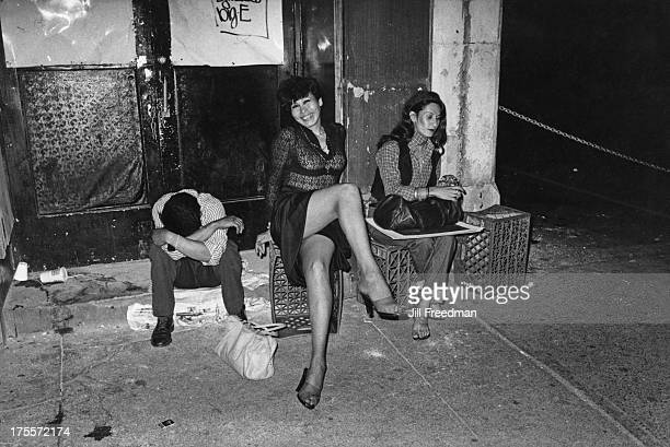 A transvestite strikes a pose amongst two tired party revellers outside Studio 54 at 5 am New York City 1979