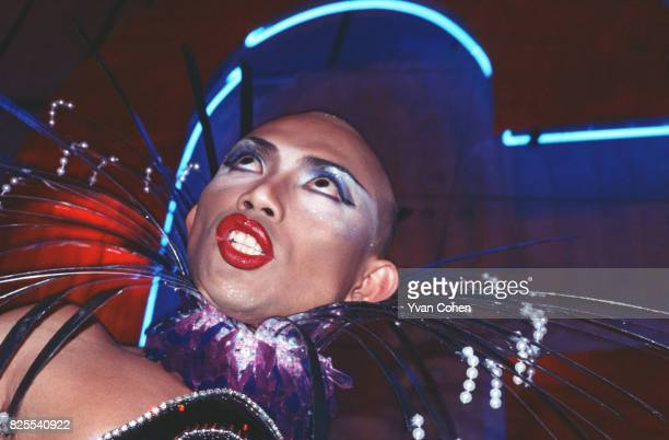 A transvestite with a shaved head and wearing heavy makeup strikes a dramatic pose as he competes in a beauty contest in a nightclub in downtown...