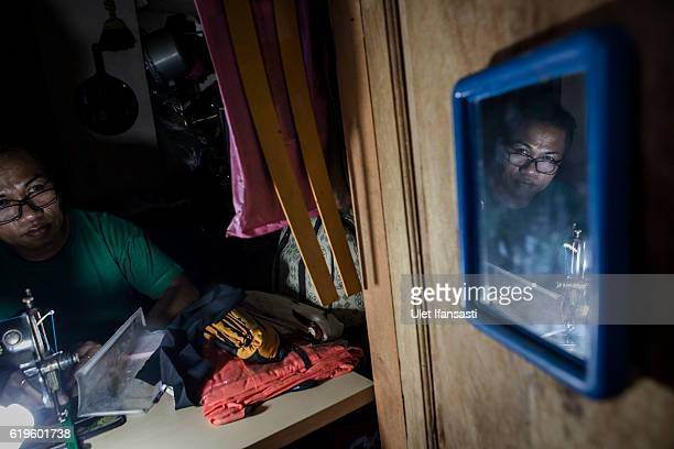 A transvestite Yanti sewing a cloth inside her house Yanti has joined the group for 22 years in a traditional dance opera group called Ludruk Karya...