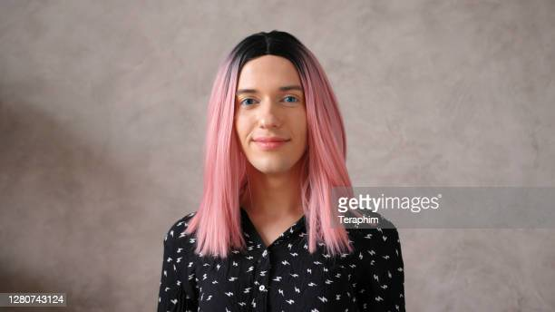 transwoman in black dot dress with pink wig poses on beige - androgynous stock pictures, royalty-free photos & images