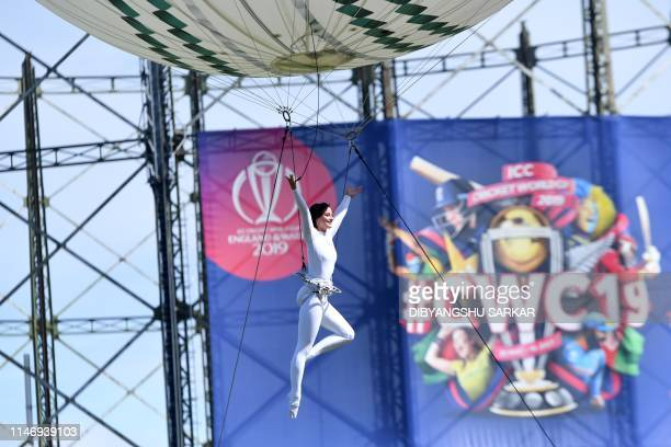 A trapeze artist holding the Winner's Trophy dangles from a balloon as balloons featuring the colours of the competing nations are displayed during...