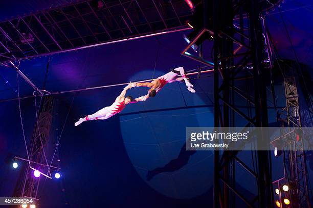 Trapeze artist swinging on a trapeze to catch another aerial artist during a circus performance on June 15 in Bonn Germany Photo by Ute...