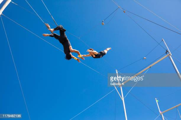 trapeze artists flying in the blue sky - trust stock pictures, royalty-free photos & images