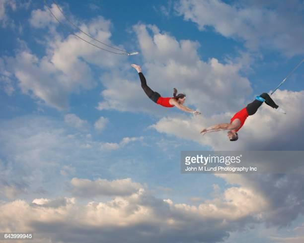 trapeze artists jumping in sky - trapeze artist stock photos and pictures