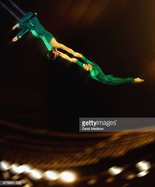 trapeze artists performing in stadium (digital composite) - trapeze artist stock photos and pictures