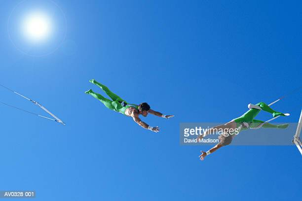 Trapeze artists performing under blue sky, view from below