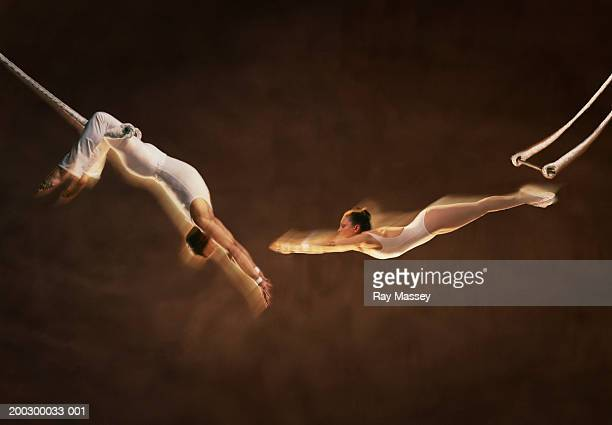 Trapeze artist's, woman stretching for man's hands (Digital Composite)