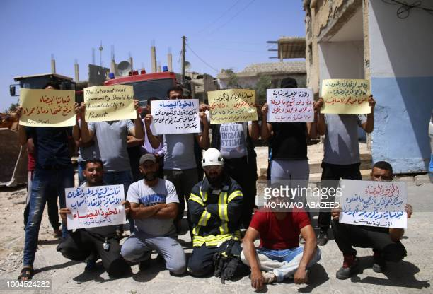 Trapped White Helmet rescue workers hold up signs urging the international community to help evacuate them from conflict areas during a sit-in in the...