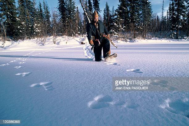 Trapper in Alaska United States walking in the snow with snowshoes