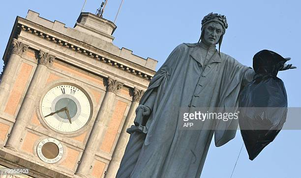 A trash bag hangs on the statue of Italian poet Dante Alighieri during a protst as part of Munnezza Day in Naples on February 23 2008 The southern...