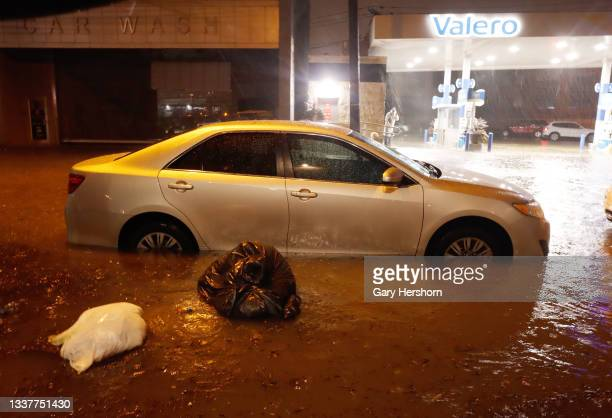 Trash bags float past a car sitting in floodwaters on Newark Street caused by the remnants of Hurricane Ida drenching the New York City and New...