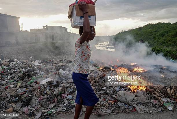 Trash burns near a sewage canal in PortAuPrince Haiti on June 8 2016 Trash collection is limited and in most places heaps of trash are eventually...