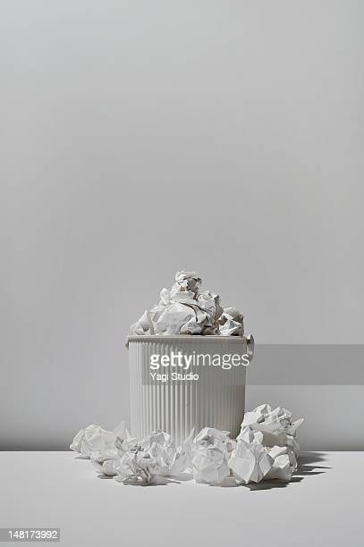 Trash can and paper trash on white background