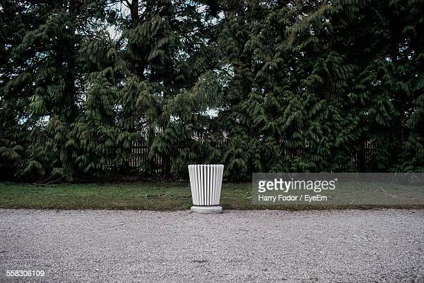 trash can beside footpath - garbage can stock photos and pictures