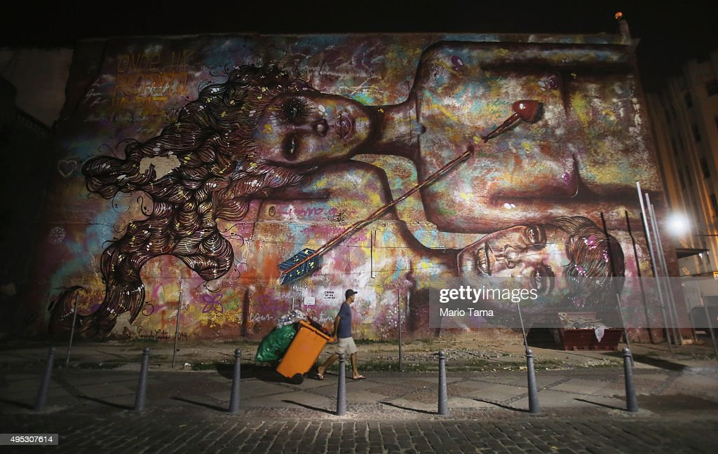 A trash collector walks past graffiti created by Panmela Castro signifying the fight against domestic violence on November 1, 2015 in Rio de Janeiro, Brazil. The city has a progressive policy towards street art and graffiti is legalized on certain city properties.