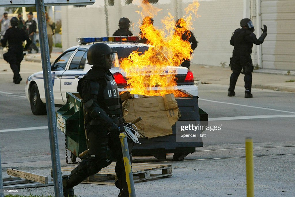 A trash fire, set by anti-globalization protesters, burns as police in riot gear stand by on the fourth day of the summit to create a Free Trade Area of the Americas November 20, 2003 in Miami, Florida. Hundreds of protesters, including a group of anarchists, clashed with police throughout the morning as they unsuccessfully tried to make their way to the Hotel Inter-Continental where the summit was taking place. Protesters say the pact would damage the environment, exploit workers overseas and cost many Americans their jobs. (Photo by Spencer Platt/Getty Images) MIAMI- NOVEMBER- 20: Police in riot gear clash with anti globalization protesters clash November 20, 2003 on the fourth day of the summit to create a Free Trade Area of the Americas (FTAA) being held in Miami, Florida. Hundreds of protesters, including groups of anarchists, clashed with the police throughout the morning as the protesters unsuccessfully tried to make their way to the summit building. Much of the city of Miami is in a police lockdown, with thousands of businesses closed and a steel barricade circling the summit area.