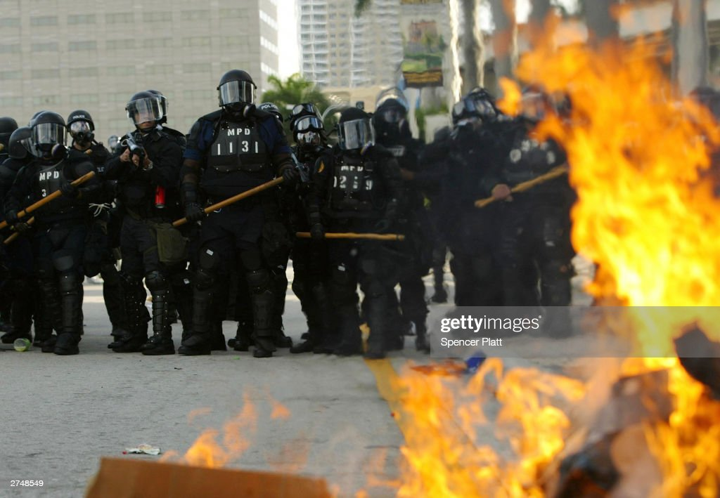 A trash fire, set by anti-globalization protesters, burns as police in riot gear stand by on the fourth day of the summit to create a Free Trade Area of the Americas November 20, 2003 in Miami, Florida. Hundreds of protesters, including a group of anarchists, clashed with police throughout the morning as they unsuccessfully tried to make their way to the Hotel Inter-Continental where the summit was taking place. Protesters say the pact would damage the environment, exploit workers overseas and cost many Americans their jobs.