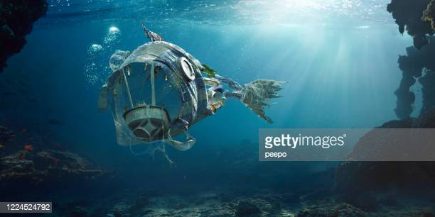 trash in sea in shape of open mouthed monster fish - packaging stock pictures, royalty-free photos & images