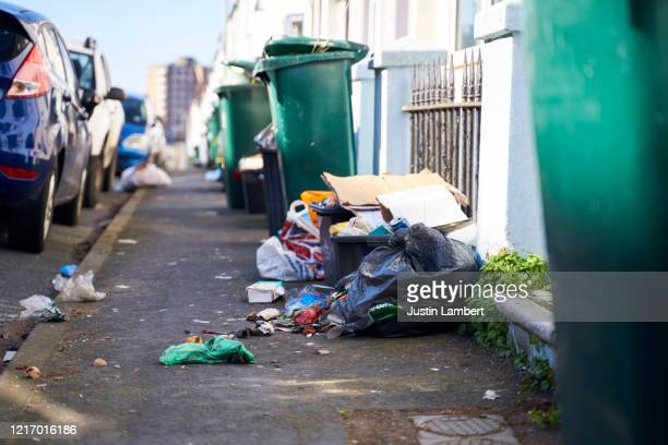 trash in the street spilling on to the pavement - rubbish stock pictures, royalty-free photos & images
