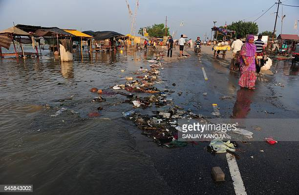 Trash is brought up to a road by flood waters after the river Ganges rose above its banks following heavy monsoon rains in Allahabad on July 10 2016...