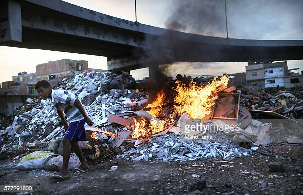 Trash is burned in an area where garbage is dumped near the main highway linking Rio's international airport to the city in the Mare favela community...