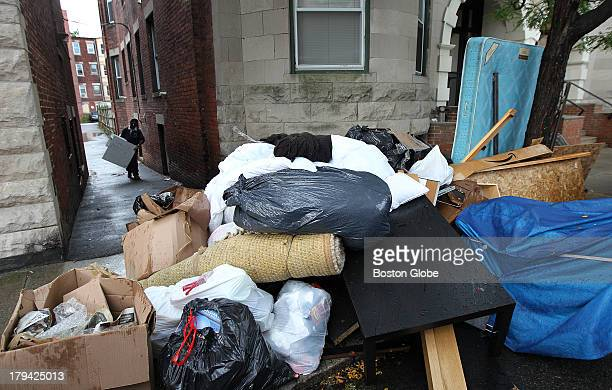 Trash left outside behind a building by former tenants is piled up near the curb on Brainerd Road by the building's management for pickup On a wet...