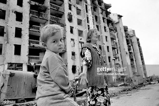 A traumatised child and his grandmother outside their devastated shell damaged apartment block During the 47 months between the spring of 1992 and...