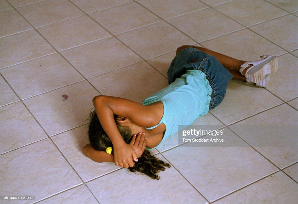 Brazil, Rio de Janeiro, Leblon district, girl (8-9) sleeping on tiled floor in homeless shelter : News Photo