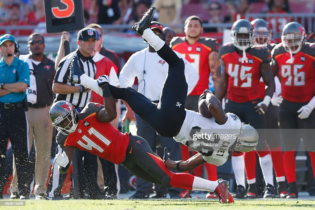Travaris Cadet #39 of the New Orleans Saints gets tripped up along the sideline by C.J. Wilson #41 of the Tampa Bay Buccaneers in the second half of the game at Raymond James Stadium on December 28, 2014 in Tampa, Florida. The Saints defeated the Bucs 23-20.