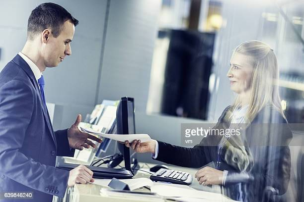 travel agent handing travel plan to a man in suit - cashier stock pictures, royalty-free photos & images