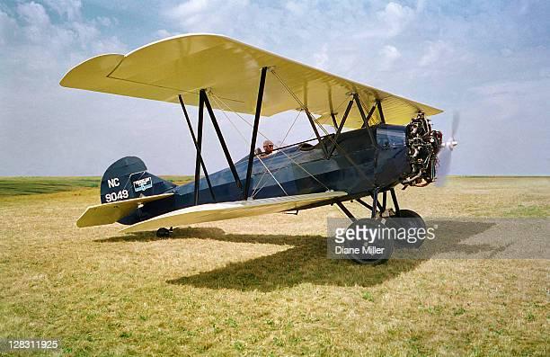 1928 travel air 4000 bi-plane on grass runway - doppeldecker flugzeug stock-fotos und bilder