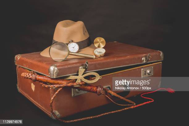 travel and advanture concept vintage brown suitcase with clock, fedora hat, bullwhip, compass, - indiana stock-fotos und bilder